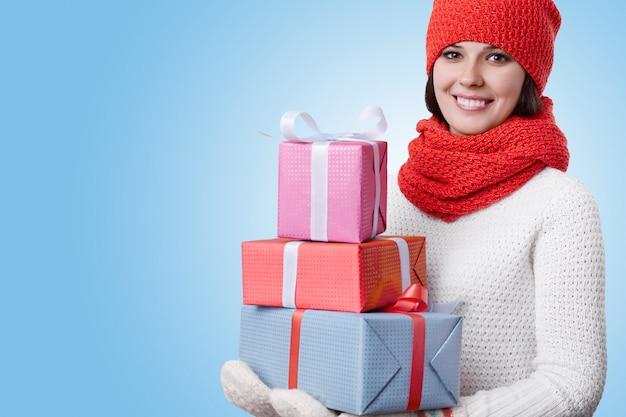 Donna che indossa cappello rosso con sciarpa maglione bianco e guanti caldi essendo felice tenendo molti regali nelle sue mani