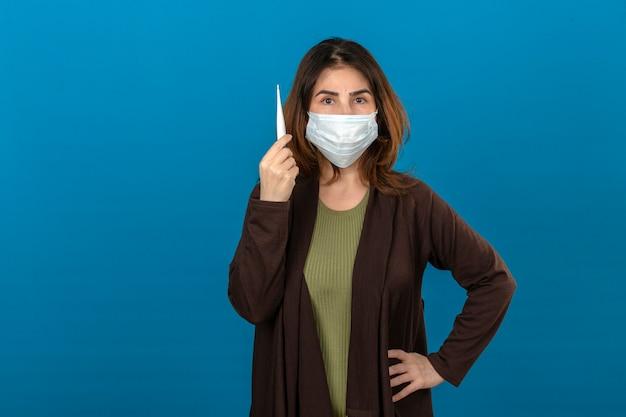 Donna che indossa cardigan marrone in maschera protettiva medica tenendo in mano il termometro digitale con la faccia seria sopra la parete blu isolata