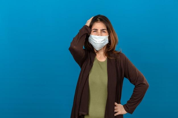 Donna che indossa cardigan marrone nella mascherina protettiva medica che sembra indisposta e testa commovente malata che soffre dal dolore sopra la parete blu isolata