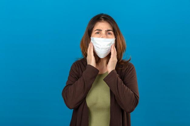 Donna che indossa cardigan marrone nelle guance commoventi della maschera protettiva medica con le mani che soffrono dal dolore sopra la parete blu isolata