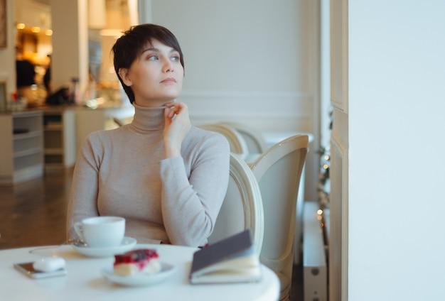 Donna che indossa dolcevita beige che si siede in caffè che guarda attraverso la finestra