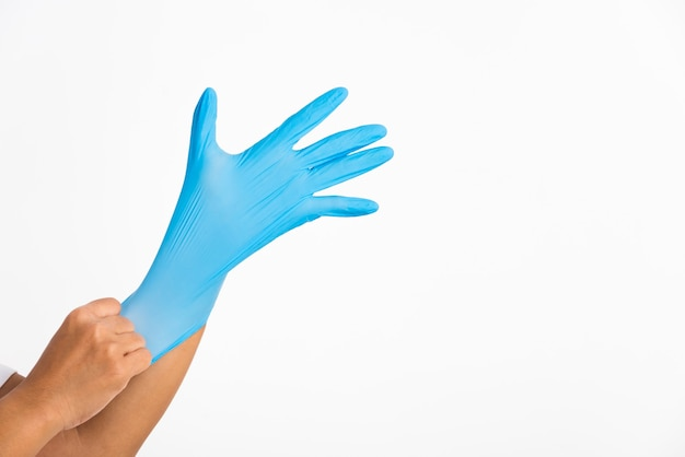 Donna che indossa e mette mano al guanto di lattice di gomma blu per il medico