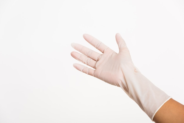 Donna che indossa e mette mano al guanto medico chirurgico in lattice di gomma bianca per medico