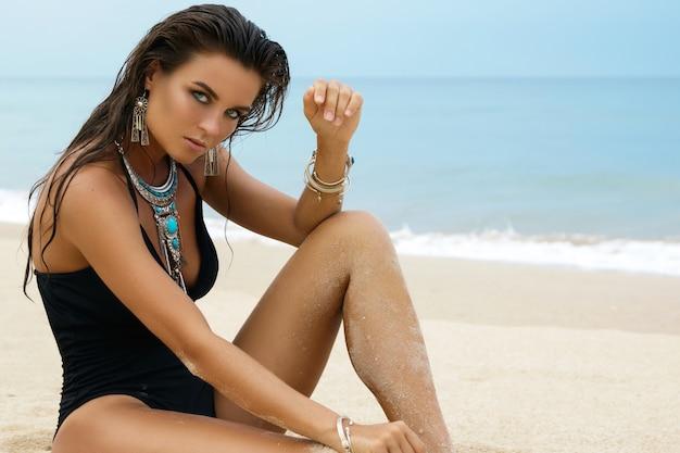 Donna che indossa gioielli d'argento sulla spiaggia