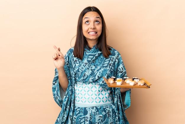 Donna che indossa kimono e che tiene i sushi sul muro con le dita che attraversano e desiderano il meglio