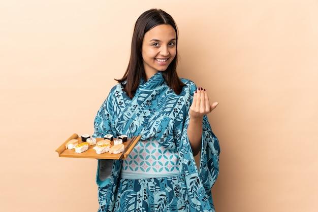 Donna che indossa kimono e che tiene i sushi sul muro invitando a venire con mano. felice che tu sia venuto