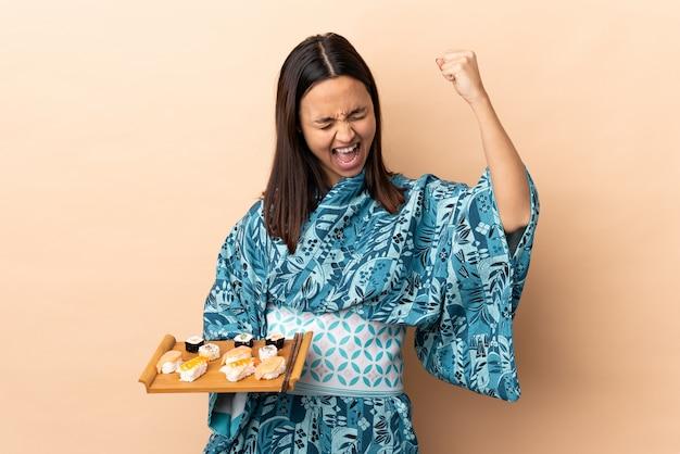 Donna che indossa kimono e che tiene i sushi sul muro per celebrare una vittoria