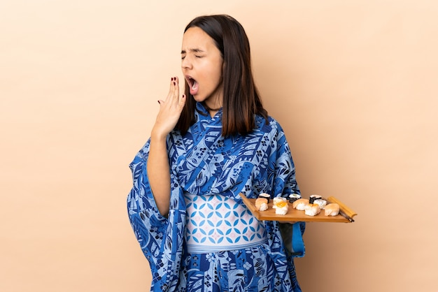 Donna che indossa kimono e che tiene i sushi sul muro sbadigliando e che copre la bocca spalancata con la mano