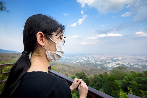 Donna che indossa la protezione facciale della maschera medica chirurgica sul punto di vista sulle montagne sulla città di chiang mai, previene il concetto di covid-19