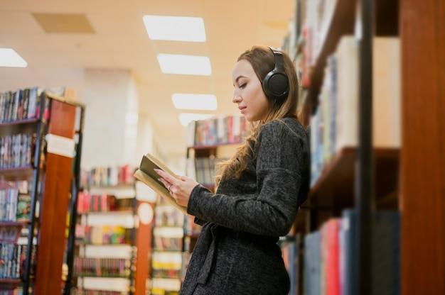 Donna che indossa le cuffie intorno al libro di lettura del collo