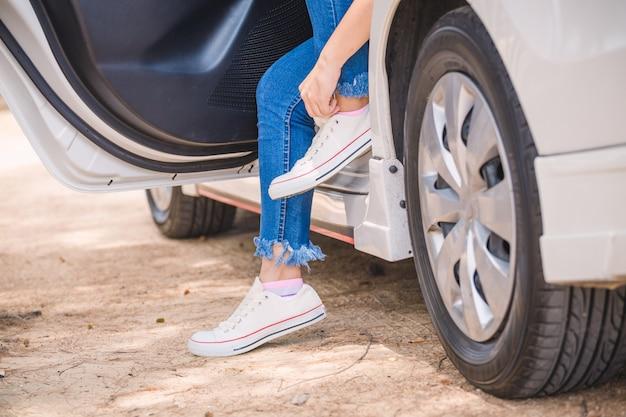 Donna che indossa le scarpe da ginnastica in auto sul lato della strada
