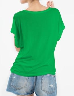 Donna che indossa maglietta verde e brevi jeans dello strappo su bianco