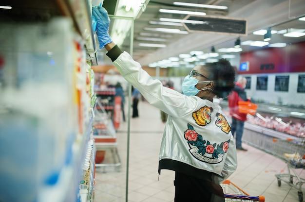 Donna che indossa maschera medica monouso e guanti shopping nel supermercato durante l'epidemia di pandemia di coronavirus.