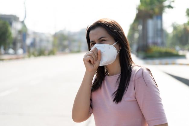 Donna che indossa maschera protettiva e tosse, coronavirus e combattimenti di pm 2.5