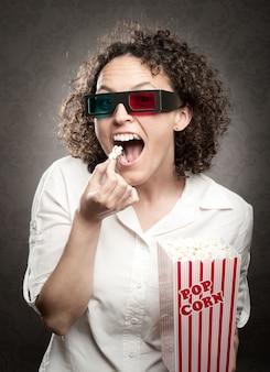 Donna che indossa occhiali 3d e mangiare popcorn