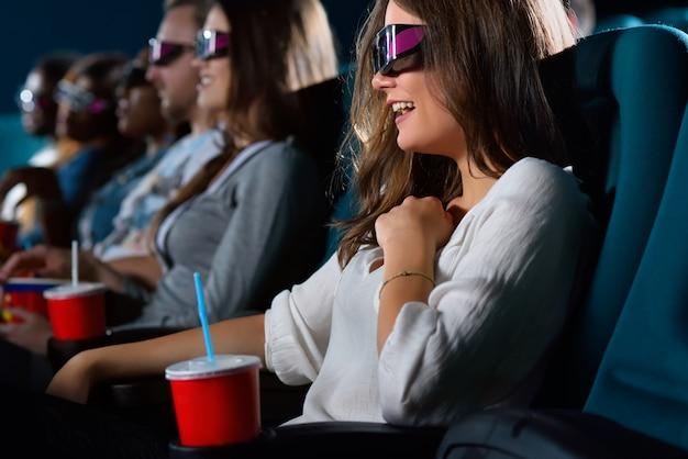 Donna che indossa occhiali 3d ridendo mentre si guarda un film