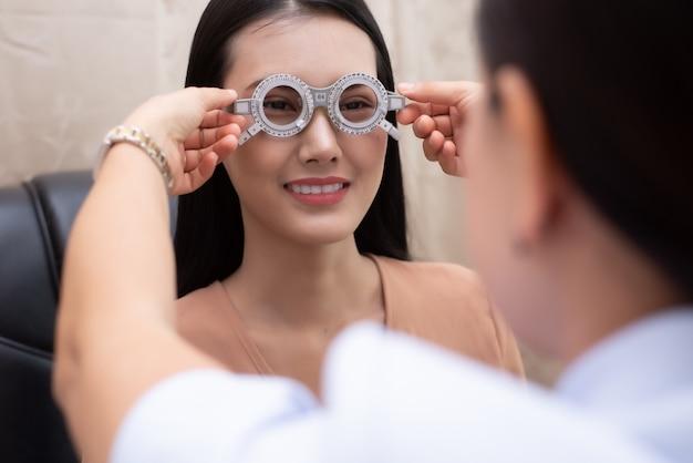 Donna che indossa occhiali dopo aver eseguito un test di visione presso il medico