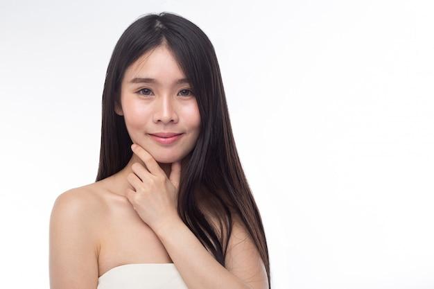 Donna che indossa un abito bianco senza spalline e le mani toccando il mento.