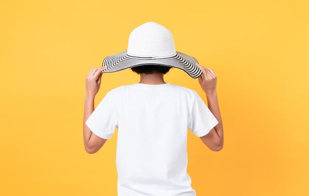 Donna che indossa un cappello a tesa larga su uno sfondo giallo
