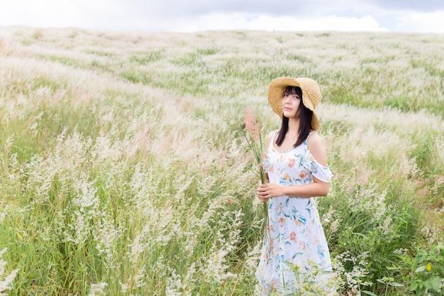 Donna che indossa un cappello, indossa un abito bianco, in piedi in mezzo all'erba con bellissimi fiori bianchi con un umore rilassato e felice.