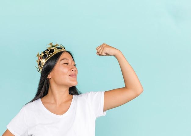 Donna che indossa una corona e alzando il braccio