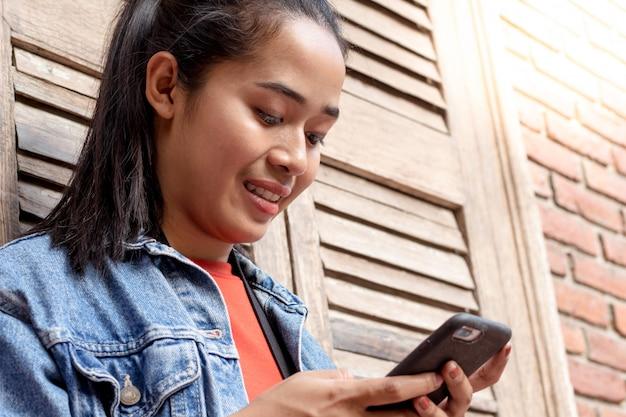 Donna che indossa una giacca e giocare con il telefono cellulare