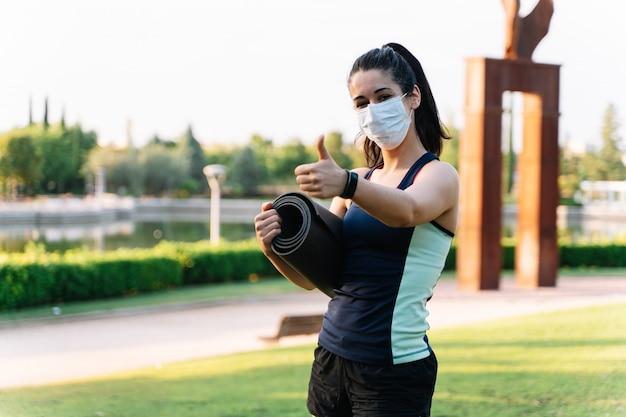 Donna che indossa una maschera e abbigliamento sportivo gesticolano per stare bene con un materasso arrotolato in mano