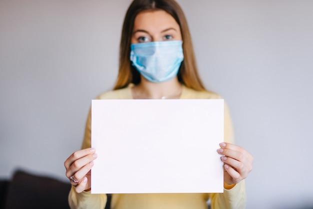 Donna che indossa una maschera medica, tenendo un foglio di carta bianco.