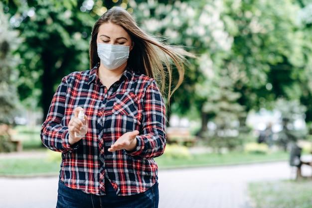 Donna che indossa una maschera protettiva e lavarsi le mani nel parco