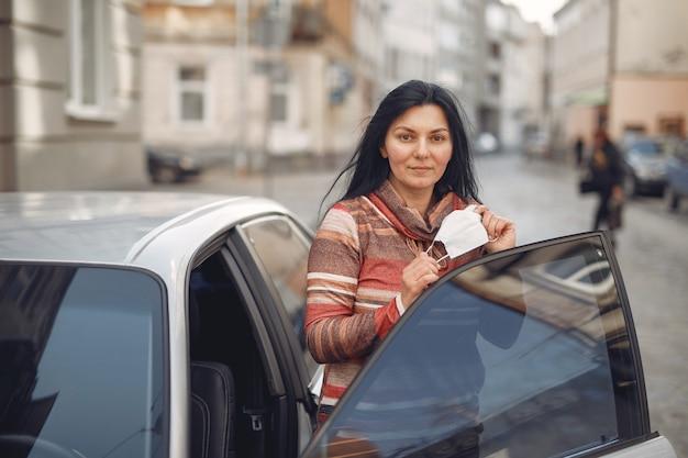Donna che indossa una maschera protettiva entrare in una macchina