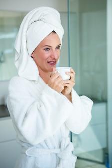 Donna che indossa una vestaglia e un asciugamano in testa sorride con una tazza e un piattino in mano
