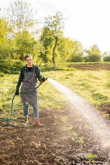 Donna che innaffia i raccolti