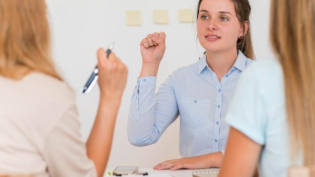 Donna che insegna ad altre due persone la lingua dei segni