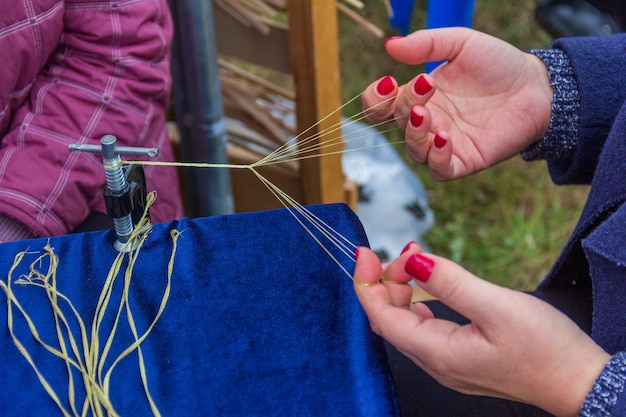 Donna che intreccia dai fili una treccia per la produzione di modelli e ornamenti circassi tradizionali