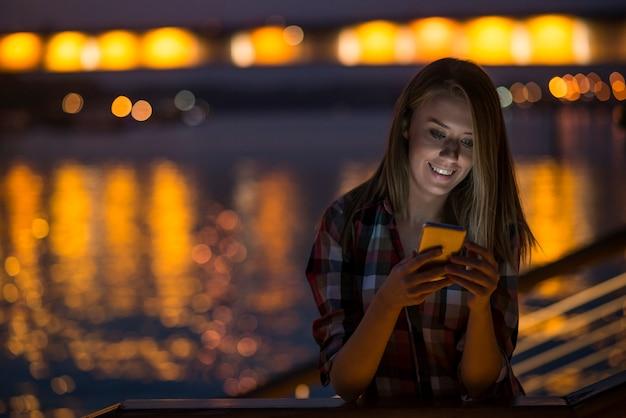 Donna che invia messaggio di testo sul telefono. ritratto di una bella gir