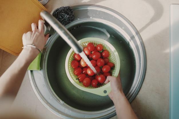 Donna che lava i pomodori degli ortaggi freschi