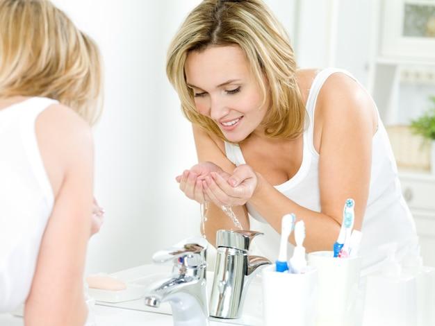 Donna che lava il viso con acqua
