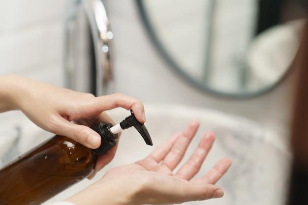 Donna che lava le mani con la bottiglia dell'erogatore del sapone al lavandino in bagno.