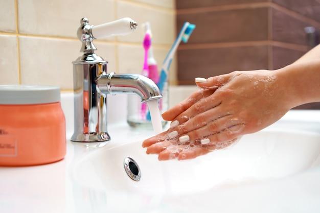 Donna che lava le sue mani con la fine del sapone in su