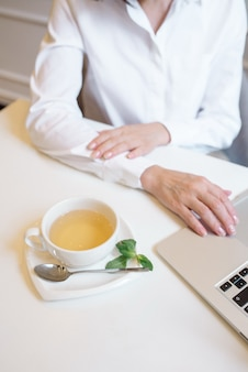 Donna che lavora a casa utilizzando laptop e bere tè verde alla menta