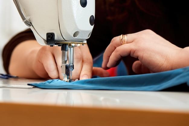 Donna che lavora ad una macchina da cucire con tessuto blu