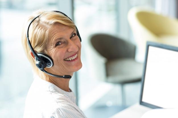 Donna che lavora al computer con l'auricolare