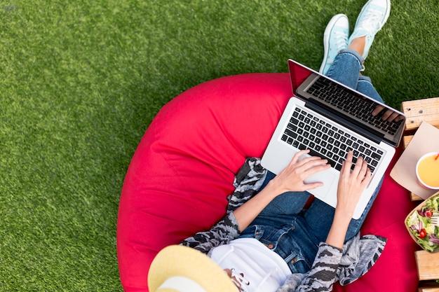 Donna che lavora al computer portatile e che mangia insalata