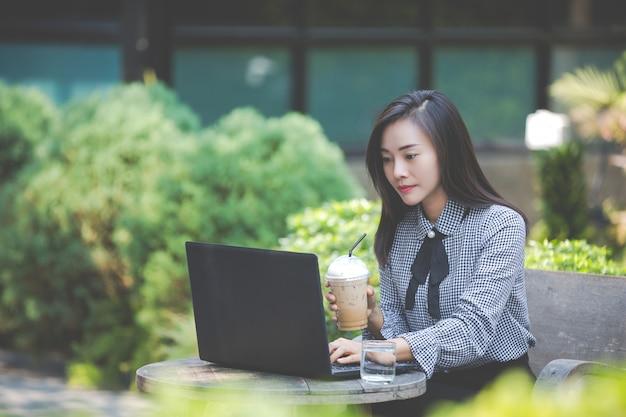 Donna che lavora al computer portatile in caffè e che beve caffè