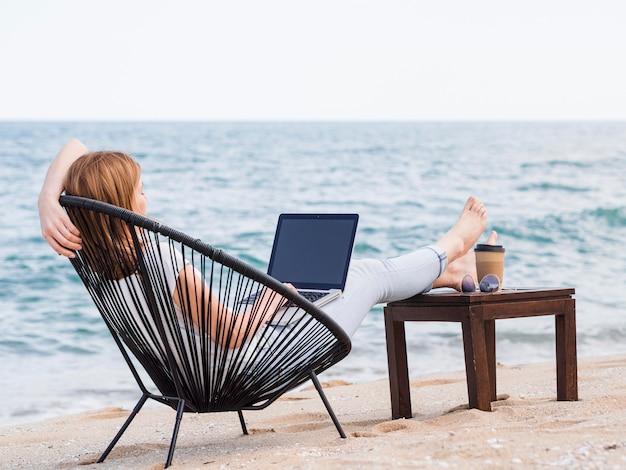 Donna che lavora al computer portatile nella sedia di spiaggia