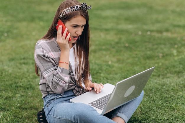 Donna che lavora con il computer portatile e lo smartphone mentre sedendosi nel giardino con erba verde. concetto di persone che utilizzano la tecnologia mobile.