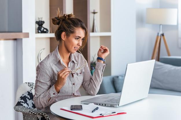 Donna che lavora con l'espressione frustrata del computer portatile a casa.