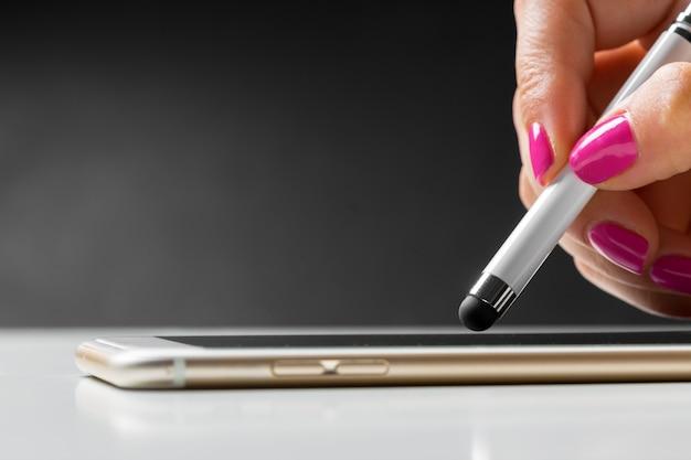 Donna che lavora con la penna sul telefono cellulare astuto