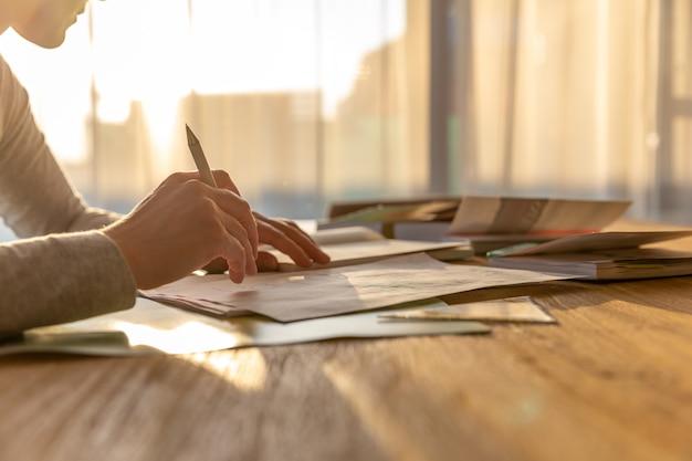 Donna che lavora da casa, scrivendo appunti da libri in un documento