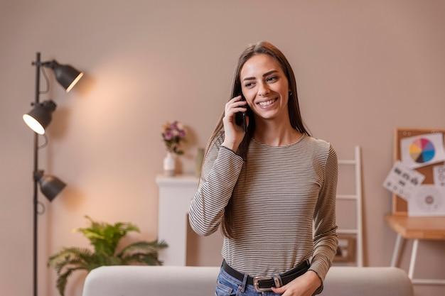 Donna che lavora e che parla sul telefono cellulare
